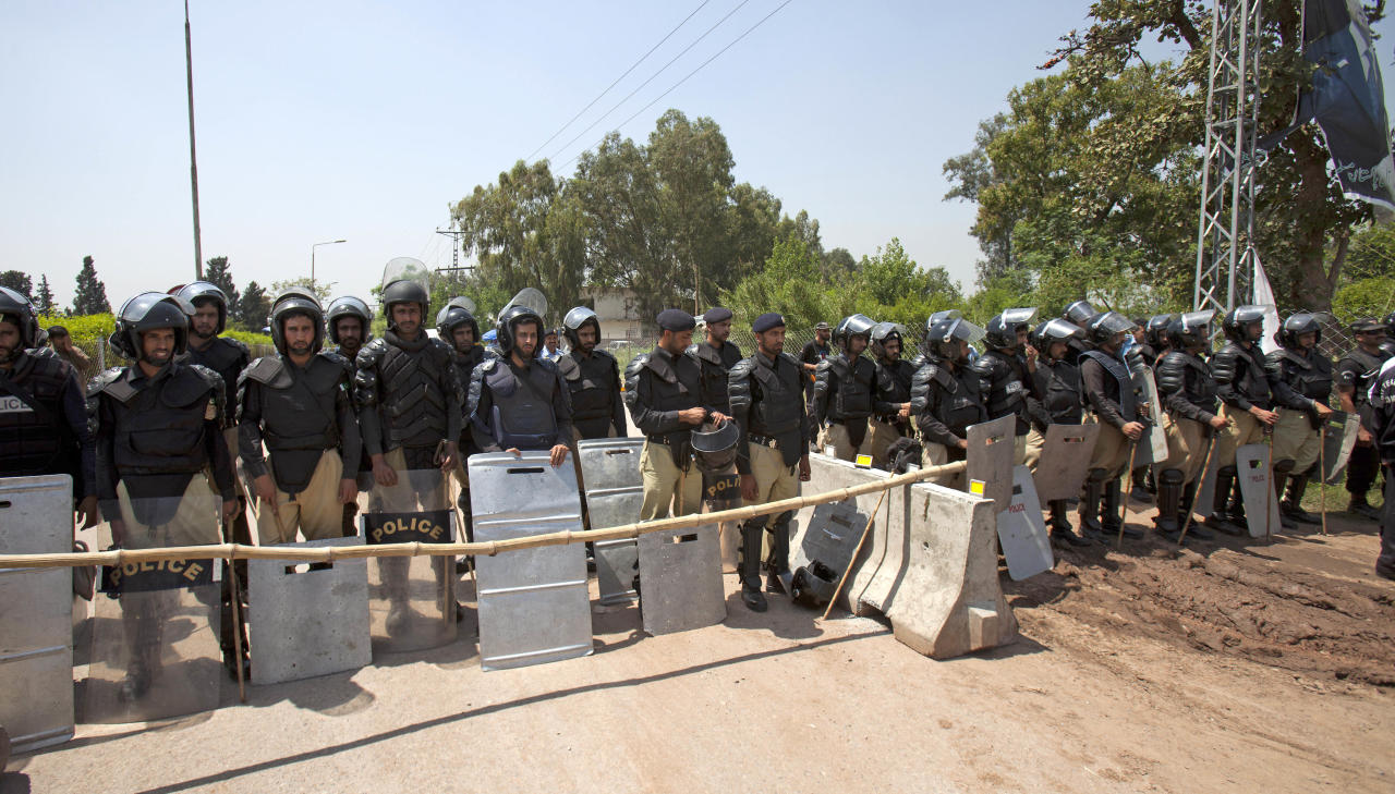 Pakistani police officers stand alert outside the house of Pakistan's former President and military ruler Pervez Musharraf in Islamabad on Thursday, April 18, 2013. Musharraf and his security team pushed past policemen and sped away from a court in the country's capital on Thursday after his bail was revoked in a case in which he is accused of treason. (AP Photo/B.K. Bangash)