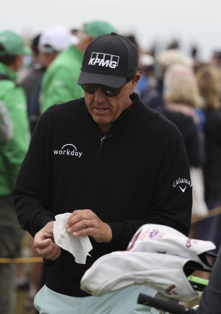 United States' Phil Mickelson wipes his hands after throwing back a fans ball that that had been offered for him to sign as he walks to the 3rd tee during a practice round for the British Open Golf Championship at Royal St George's golf course Sandwich, England, Wednesday, July 14, 2021. The Open starts Thursday, July, 15. (AP Photo/Ian Walton)