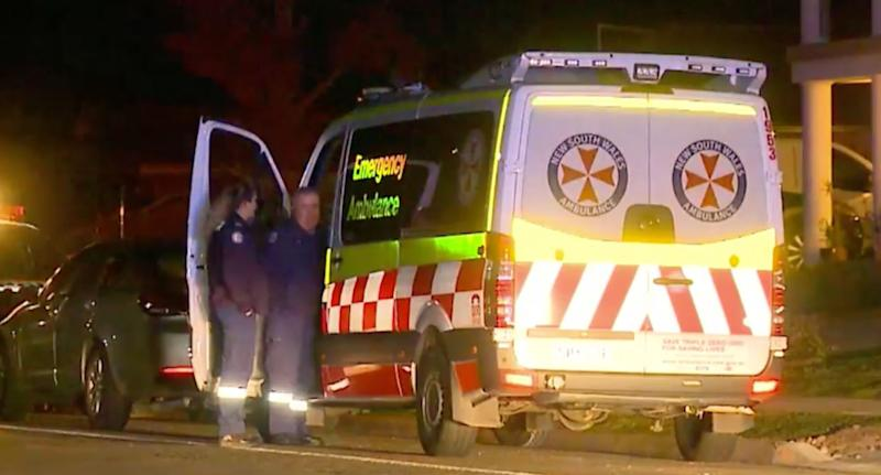 An ambulance outside a home in Sydney's west where a 57-year-old woman was allegedly decapitated in front of her grandson.