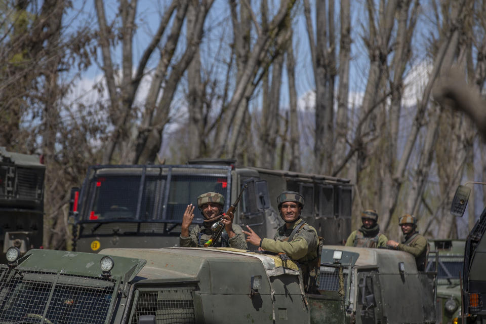 Indian army soldiers flash the victory sign as they leave the site of a gunbattle in Pulwama, south of Srinagar, Indian controlled Kashmir, Friday, April 2, 2021. Anti-India protests and clashes have erupted between government forces and locals who thronged a village in disputed Kashmir following a gunbattle that killed three suspected militants. Police say the gunfight on Friday erupted shortly after scores of counterinsurgency police and soldiers launched an operation based on tip about presence of militants in a village in southern Pulwama district. (AP Photo/ Dar Yasin)