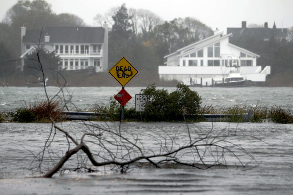 A downed limb lies in a flooded street as Hurricane Sandy approaches, Monday, Oct. 29, 2012, in Center Moriches, N.Y. Hurricane Sandy continued on its path Monday, as the storm forced the shutdown of mass transit, schools and financial markets, sending coastal residents fleeing, and threatening a dangerous mix of high winds and soaking rain. (AP Photo/Jason DeCrow)