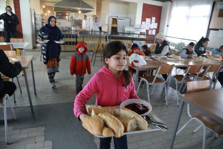 Sonya, 8, daughter of Afghan refugee Najibullah, carries food at the camp for refugees and migrants in the Belgrade suburb of Krnjaca