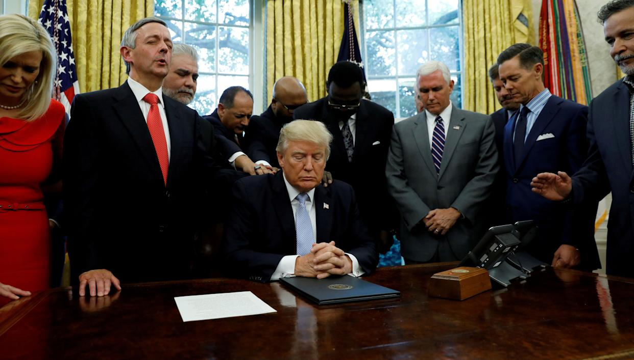 Faith leaders place their hands on the shoulders of President Donald Trump as he takes part in a prayer for those affected by Hurricane Harvey in the Oval Office on Sept. 1, 2017. (Photo: Kevin Lamarque / Reuters)