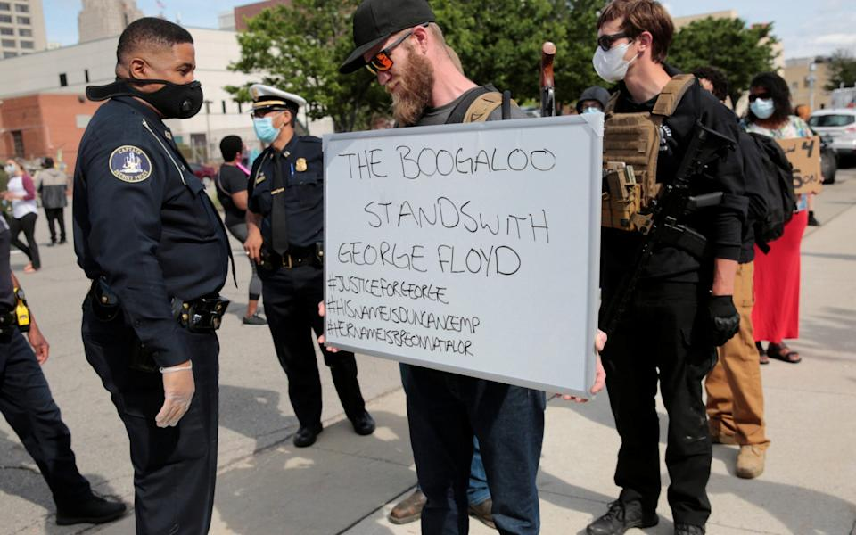 "A Detroit Police officer reads a ""The Boogaloo stands with George Floyd"" sign held by an armed man during a rally against the death in Minneapolis police custody of George Floyd, in Detroit, Michigan, U.S. May 30, 2020. - Rebecca Cook/Reuters"