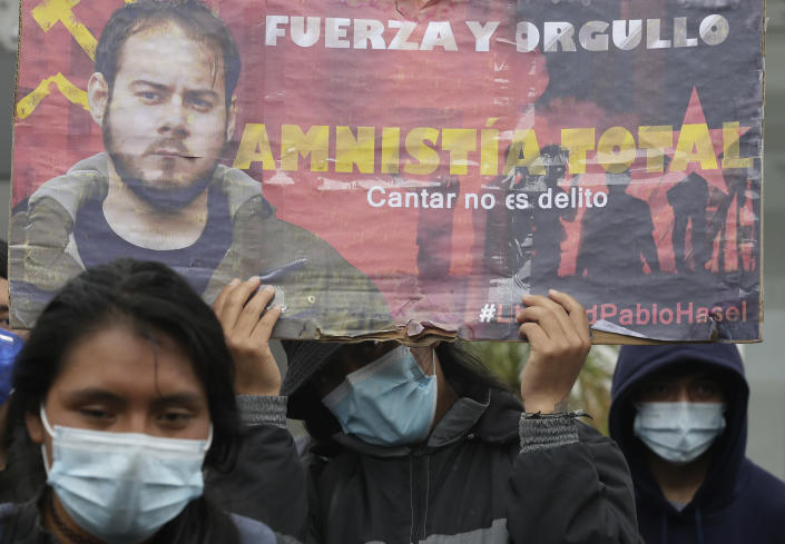 """Demonstrators protest Spain's arrest of rap singer Pablo Hasel, convicted of insulting the Spanish monarchy and praising terrorist violence, outside Spain's consulate in Quito, Ecuador, Friday, Feb. 19, 2021. The sign reads in Spanish """"Strength and Pride. Total amnesty. Singing is not a crime."""" (AP Photo/Dolores Ochoa)"""