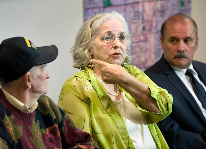 Jan Cooper, 72, talks to the media as her husband Bob, 85, left, and OC Sheriff's spokesman Jim Amormino listen during a news conference at the Sheriff's Department station in Stanton on Tuesday, June 11, 2013. Jan Cooper showed where the Sheriff's estimated the bullet traveled, based on the size of the suspect and the damage to her sliding glass door, when she scared off an intruder at her home in unincorporated Anaheim on Sunday, June 9, by firing a shot from her .357 Magnum during the attempted break-in. The bullet went through the frame of her sliding glass door and just missed the intruder. The suspect, Brandon Alexander Perez, is in custody. (AP Photo/The Orange County Register, Paul Bersebach) MANDATORY CREDIT THE ORANGE COUNTY REGISTER, LA TIMES, MAGS OUT