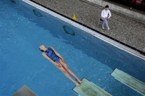 A member of Crystal Palace diving club dives watched by coach Xiang Yan Kong during a training session in London March 9, 2012.