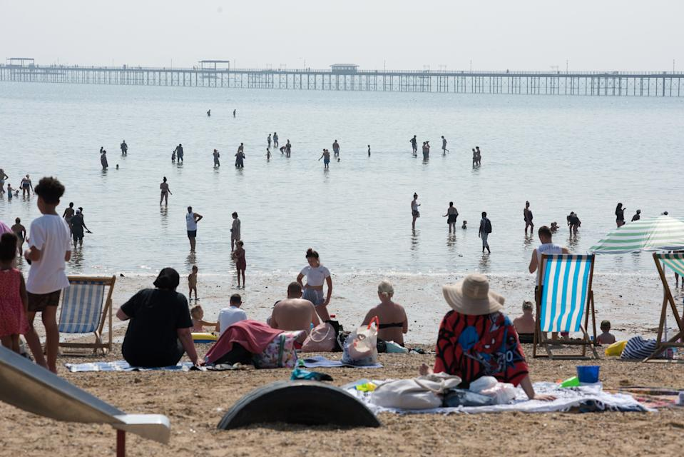 SOUTHEND-ON-SEA, ENGLAND AUGUST 11: People walk out from the beach at low tide to cool down in the water during the recent hot weather on August 11, 2020 in Southend on Sea, England. Parts of the UK remain in the grip of a Summer heatwave that has seen temperatures rise above 30 degrees in much of the country. (Photo by John Keeble/Getty Images)