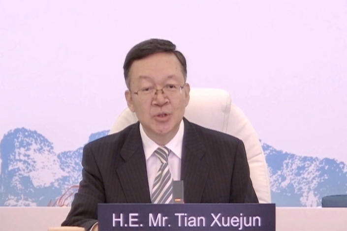 """In this image taken from video footage run by UNESCO via AP Video, Vice Minister of Education Tian Xuejun, center, who is also Director of the Chinese National Commission for UNESCO speaks during a press conference for the 44th session of the World Heritage Committee of UNESCO in Fuzhou in southeast China's Fujian Province, Sunday, July 18, 2021. The Chinese host of this year's meeting of the U.N, World Heritage Committee defended on Sunday the body's proposal to label the Great Barrier Reef as """"in danger"""" against Australian government suspicion that China influenced the finding for political reasons. Tian Xuejun said Australia should attach importance to the opinions of advisory bodies instead of making groundless accusations. (UNESCO via AP Video)"""