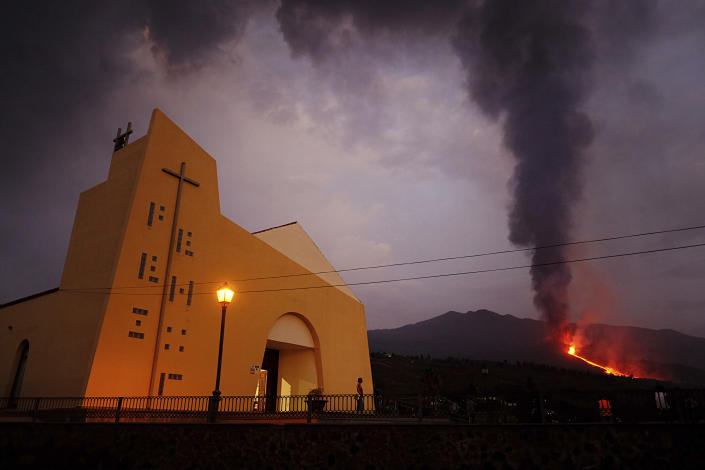 Lava flows from a volcano on the Canary island of La Palma, Spain on Monday Sept. 27, 2021. A Spanish island volcano that has buried more than 500 buildings and displaced over 6,000 people since last week lessened its activity on Monday, although scientists warned that it was too early to declare the eruption phase finished and authorities ordered residents to stay indoors to avoid the unhealthy fumes from lava meeting sea waters. (AP Photo/Daniel Roca)
