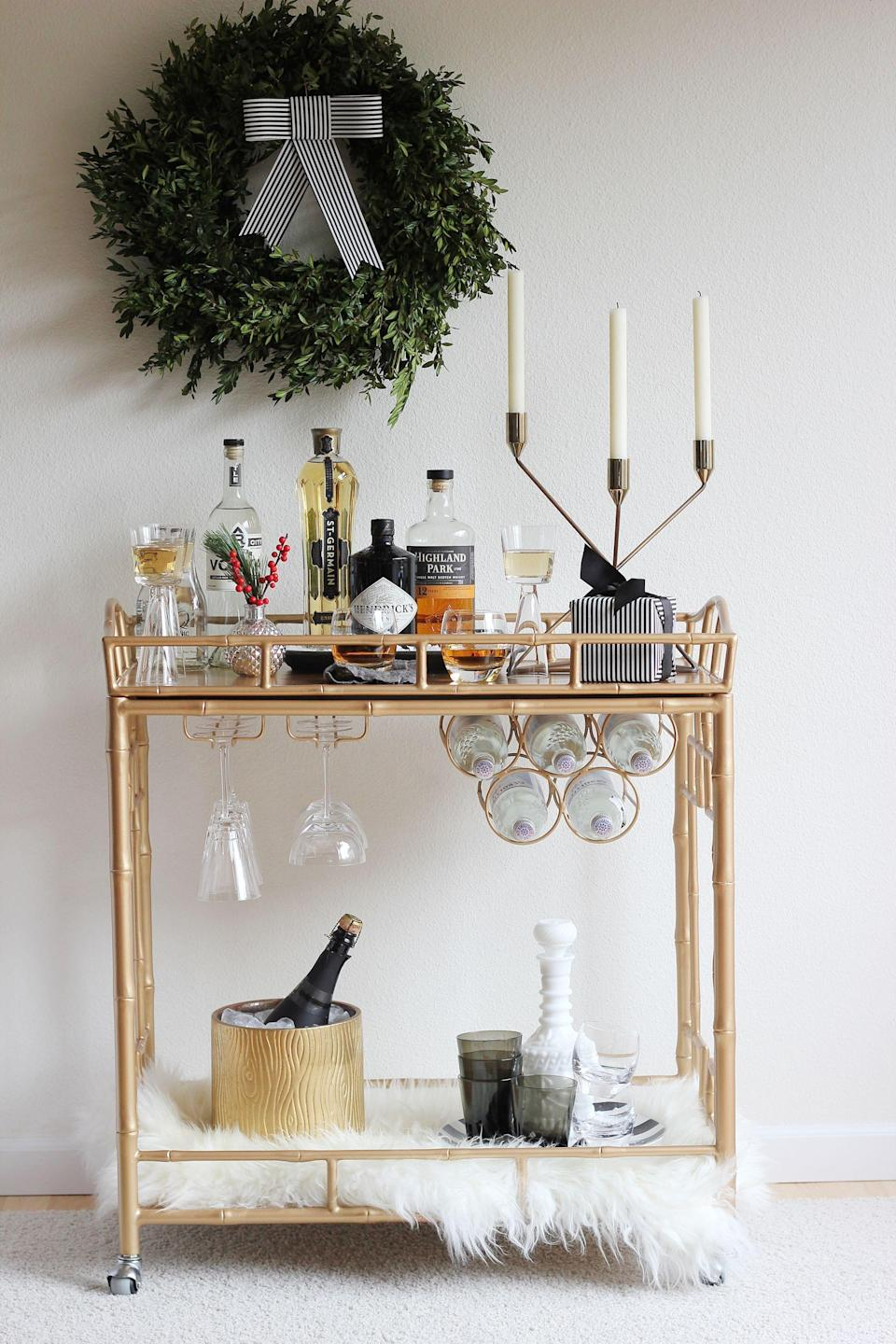 """<p>For a pared-down New Year's look, set up an old-fashioned brass bar cart worthy of Ernest Hemingway, ala <a rel=""""nofollow noopener"""" href=""""https://jennybatt.com/blog/an-easy-diy-paper-bow-for-your-holiday-bar-cart"""" target=""""_blank"""" data-ylk=""""slk:Hank & Hunt"""" class=""""link rapid-noclick-resp"""">Hank & Hunt</a>, and go light on the holiday touches. A few tapers and sprigs of greenery are all it needs. </p>"""