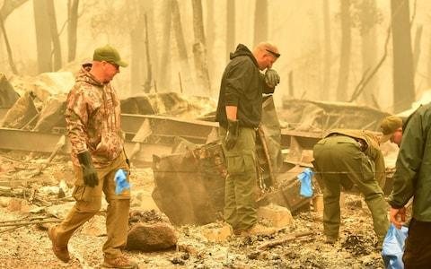 <span>Yuba and Butte County Sheriff officers react as they discover a body at a burned out residence after the Camp fire tore through the area in Paradise</span> <span>Credit: AFP </span>
