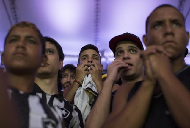In this April 2, 2014 photo, fans of the Botafogo soccer team watch a Copa Libertadores soccer match at Maracana stadium in Rio de Janeiro, Brazil. Soccer's big moment happens in June as the best players on the planet meet in Brazil for the World Cup. In Brazil, soccer is a unifying force. (AP Photo/Leo Correa)
