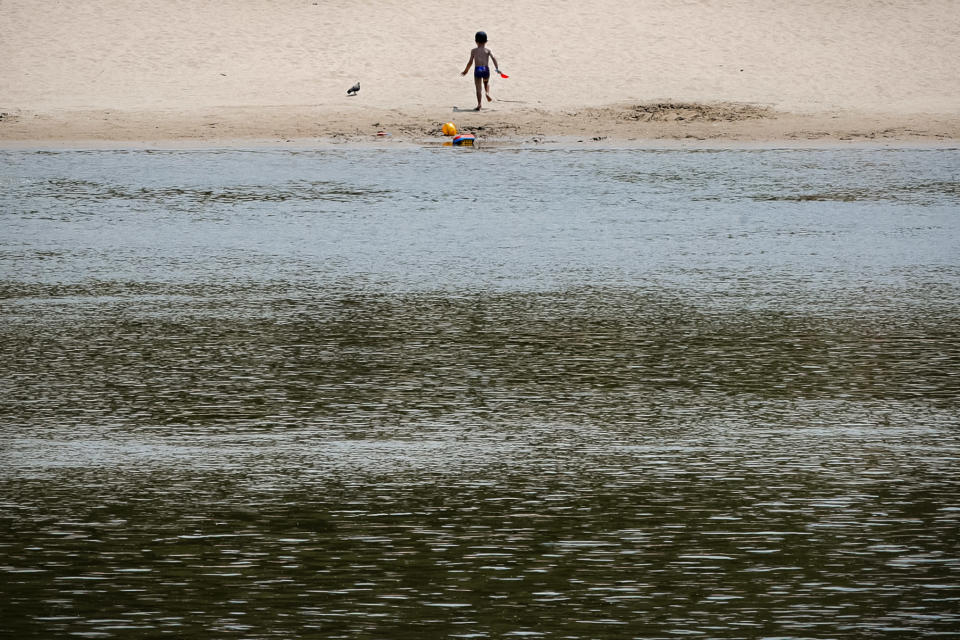 A small child runs on a beach on the river Danube banks in Calarasi, southern Romania, the hometown of Claudia Anghel, a Romanian midwife working in England, on Monday, July, 27, 2020. Romania joined the European Union in 2007 and, by 2013, more than 14,000 Romanian doctors were working abroad, about 26% of the country's total number of physicians. (AP Photo/Vadim Ghirda)