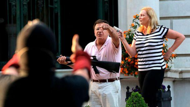 PHOTO: Armed homeowners Mark and Patricia McCloskey, stand in front their house along Portland Place as they confront protesters marching to St. Louis Mayor Lyda Krewson's house in St. Louis, June 28, 2020. (Louis Post-Dispatch via AP, FILE)