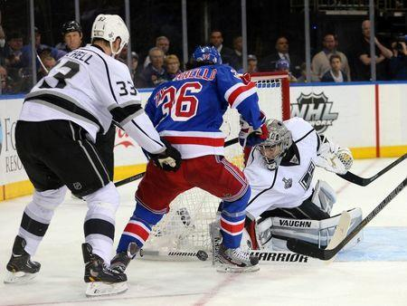 Jun 9, 2014; New York, NY, USA; Los Angeles Kings goalie Jonathan Quick (32) and defenseman Willie Mitchell (33) defend the net against New York Rangers right wing Mats Zuccarello (36) during the second period in game three of the 2014 Stanley Cup Final at Madison Square Garden. Mandatory Credit: Brad Penner-USA TODAY Sports