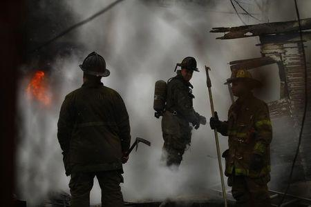 Detroit firefighters try to contain a fire at a shed in Detroit