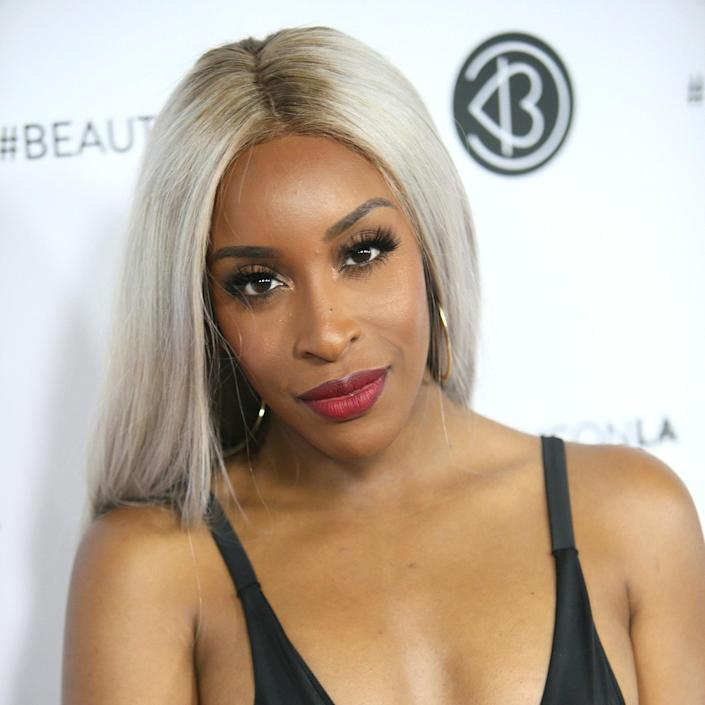 The best thing about this hue on YouTuber Jackie Aina is that it might be an ashy, grayish platinum color, but it doesn't make her skin tone <em>look</em> ashy. The dark roots help ground the color and let her golden undertone come through. As Jung notes, if your natural hair is as dark as Aina's, you might want to experiment with a platinum wig to keep your hair healthy. This one on the beauty influencer looks especially cool with a slightly darker root.