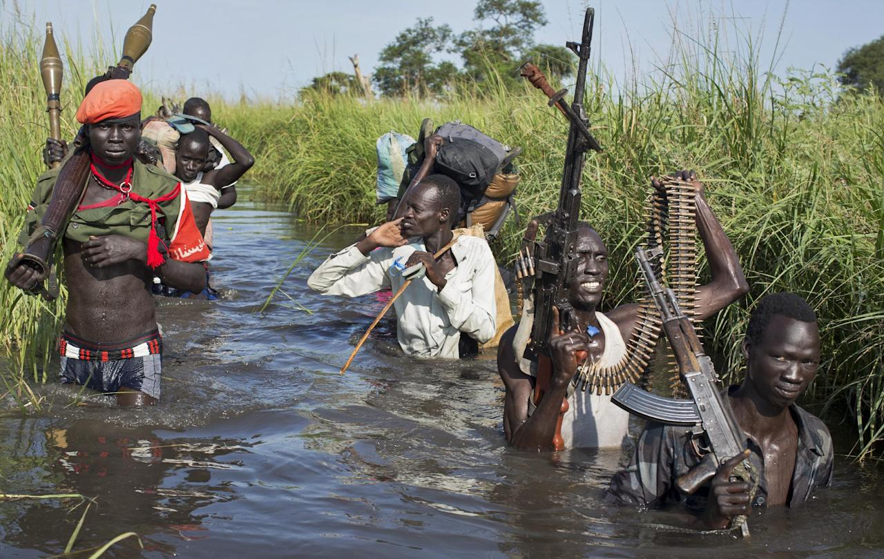 FILE - In this Saturday, Sept. 20, 2014 file photo, rebel soldiers patrol and protect civilians from the Nuer ethnic group, as the civilians walk through flooded areas to reach a makeshift camp for the displaced situated in the United Nations Mission in South Sudan (UNMISS) base in the town of Bentiu, South Sudan. Sudan's government plans to increase military assistance to rebels in South Sudan, which could prolong the south's civil war and return the region to a wider conflict, according to leaked documents that a top American expert on Sudan has concluded are real.(AP Photo/Matthew Abbott, File)