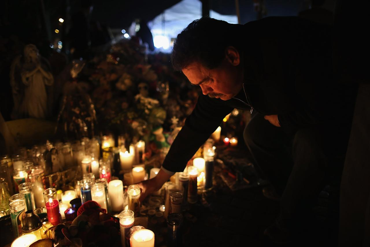 NEWTOWN, CT - DECEMBER 18:  A mourner places a candle while visiting a makeshift memorial for shooting victims on December 18, 2012 in Newtown, Connecticut. Funeral services were held in Newtown Tuesday for Jessica Rekos and James Mattioli, both age six, four days after 20 children and six adults were killed at Sandy Hook Elementary School.  (Photo by John Moore/Getty Images)