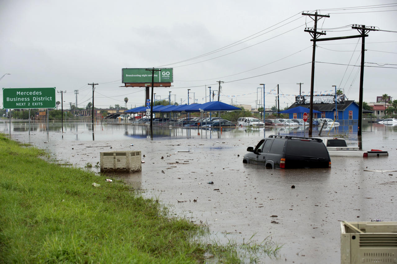 Abandoned vehicles sit in sewage-tainted floodwater Wednesday, June 20, 2018, near Mercedes, Texas. Heavy rains along the Texas coast have caused flooding in areas that were hit hard by Hurricane Harvey less than a year ago. (Jason Hoekema/The Brownsville Herald via AP)