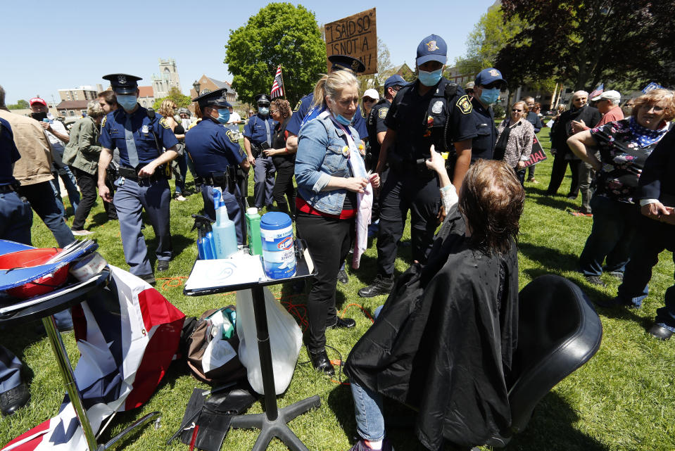 Linda Hicks, seated, points at a Michigan State Police trooper while receiving a free haircut from Teresa Luks, left, at the State Capitol during a rally in Lansing, Mich., Wednesday, May 20, 2020. Barbers and hair stylists are protesting the state's stay-at-home orders, a defiant demonstration that reflects how salons have become a symbol for small businesses that are eager to reopen two months after the COVID-19 pandemic began. (AP Photo/Paul Sancya)