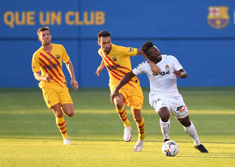 BARCELONA, SPAIN - SEPTEMBER 12: Thomas Amang of Gimnastic de Tarragona is challenged by Sergio Busquets of FC Barcelona during the during the pre-season friendly match between FC Barcelona and Gimnastic de Tarragona at Estadi Johan Cruyff on September 12, 2020 in Barcelona, Spain. (Photo by David Ramos/Getty Images)