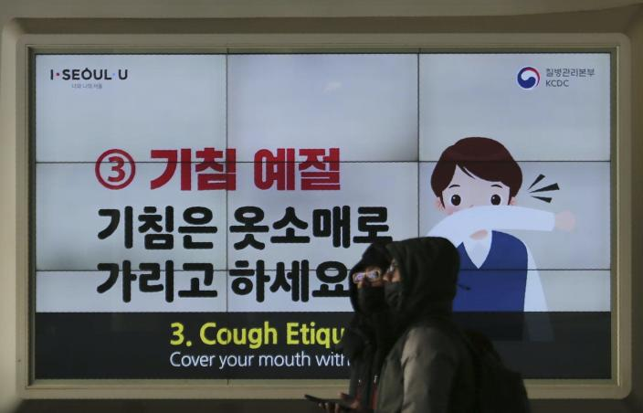 """<span class=""""caption"""">On Feb. 18, 2020, in Seoul, South Korea, people wearing face masks pass an electric screen warning about COVID-19. </span> <span class=""""attribution""""><a class=""""link rapid-noclick-resp"""" href=""""http://www.apimages.com/metadata/Index/South-Korea-China-Outbreak/cb79407a56854d69b3c3565bbc067f74/9/0"""" rel=""""nofollow noopener"""" target=""""_blank"""" data-ylk=""""slk:AP Photo/Ahn Young-joon"""">AP Photo/Ahn Young-joon</a></span>"""
