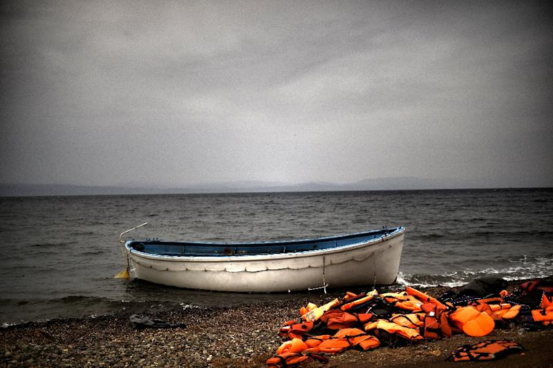 Life jackets and a boat that were used by refugees and migrants to cross the Aegean sea from Turkey lie abandoned on a beach on the Greek Island of Lesbos on October 8, 2015 (AFP Photo/Aris Messinis)