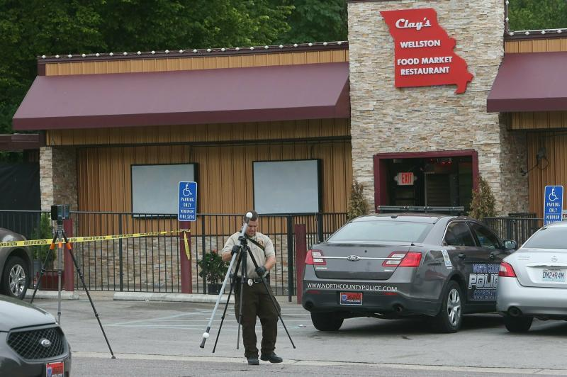 A St. Louis County crime scene investigator sets up cameras in front of Clay's Wellston Food Market Restaurant on Sunday, June 23, 2019, in Wellston, Mo., at the scene where a North County Cooperative police officer was shot inside the market. (J.B. Forbes//St. Louis Post-Dispatch via AP)