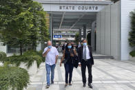 Skea Nigel, left, Agatha Maghesh Eyamalai, center, and defense lawyer Dhillon Surinder Singh leave the State Courts in Singapore, Monday, Feb. 15, 2021. Nigel, a British national, pleaded guilty on Monday to violating a coronavirus quarantine order in Singapore to visit his fiancee. (AP Photo/Annabelle Liang)