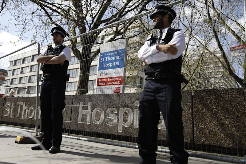 "Police officers stand in front of barriers erected outside St Thomas' Hospital in London on April 6, 2020. - British Prime Minister Boris Johnson was in hospital on Monday undergoing tests after suffering ""persistent"" symptoms of coronavirus for 10 days, but colleagues insisted he remains in charge of the government. Reports have suggested that the prime minister was admitted to nearby St Thomas' Hospital last night. (Photo by Tolga AKMEN / AFP) (Photo by TOLGA AKMEN/AFP via Getty Images)"