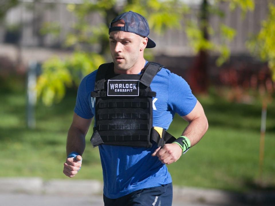 an athlete running in a weighted vest outdoors