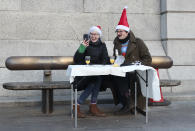 Nick and Charlie, left, speak to relatives on the phone as they have an outdoor breakfast in Trafalgar Square in London, Friday, Dec. 25, 2020. They decided to dine al fresco after their planned trip to visit family was cancelled due to the coronavirus pandemic restrictions. (AP Photo/Tony Hicks)