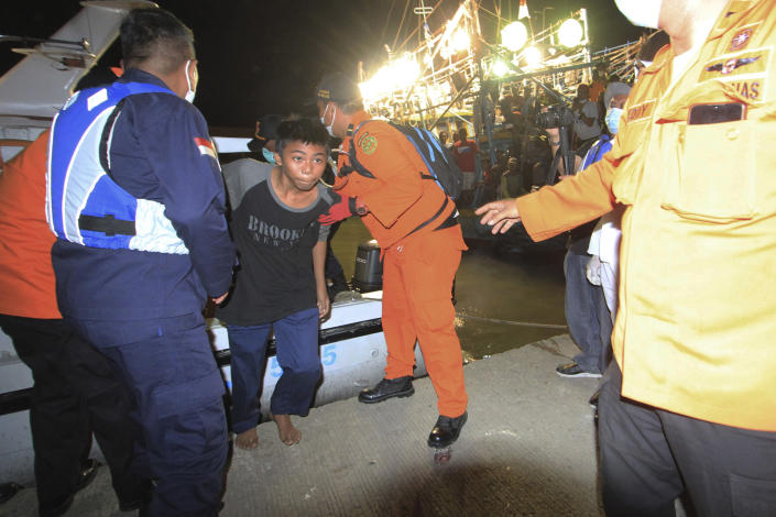 Rescuers assist one of the survivors of a ship collision, center, upon his arrival at a port in Indramayu, West java, Indonesia, Sunday, April 4, 2021. The collision between a cargo ship and a fishing boat left a number of people missing off Indonesia's main island of Java, officials said Sunday. (AP Photo/Panji Wisnu)