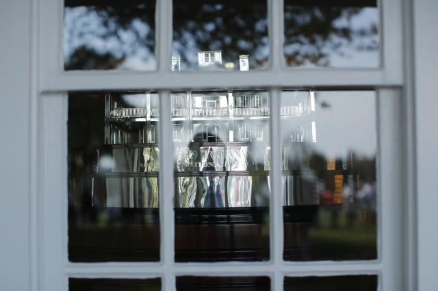 The Masters Tournament Trophy is pictured through a window at the main clubhouse during practice for the 2018 Masters golf tournament at Augusta National Golf Club in Augusta, Georgia, U.S. April 2, 2018. REUTERS/Mike Segar