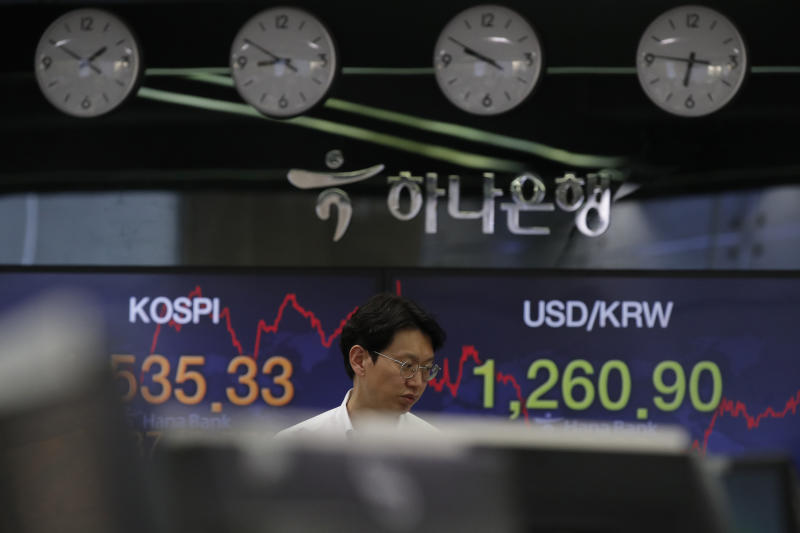 A currency trader walks by screens showing the Korea Composite Stock Price Index (KOSPI), left, and the foreign exchange rate between U.S. dollar and South Korean won at the foreign exchange dealing room in Seoul, South Korea, Tuesday, March 24, 2020. Asian stock markets gained Tuesday after the U.S. Federal Reserve promised support to the struggling economy as Congress delayed action on a $2 trillion coronavirus aid package. (AP Photo/Lee Jin-man)