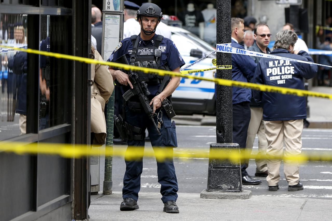 Members of the NYPD police stand near the crime scene at the intersection of 37th street and 8th avenue in midtown Manhattan in New York, May 13, 2015.  A hammer-wielding man who hit three people on the head in tourist-packed areas of New York City earlier this week has been shot in a confrontation with police, New York media reported on Wednesday.   REUTERS/Shannon Stapleton