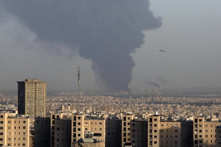 Huge smoke rises up from Tehran's main oil refinery as a plane approaches Mehrabad airport south of Tehran, Iran, Wednesday, June 2, 2021. A massive fire broke out Wednesday night at the oil refinery serving Iran's capital, sending thick plumes of black smoke over Tehran. (AP Photo/Vahid Salemi)