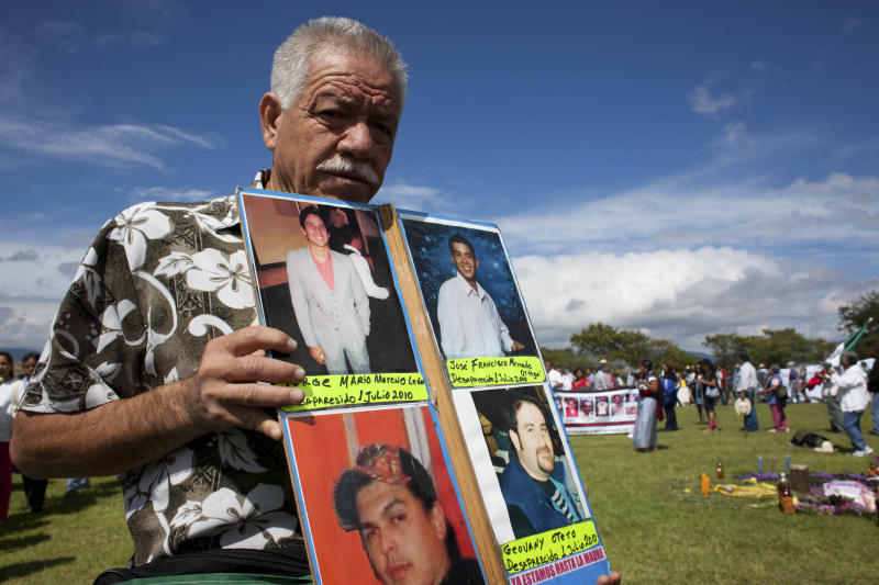 In this photo taken Sept. 12, 2011, Nepomuceno Moreno holds up images of missing people, including his son, top left, during a protest of the Peace Caravan, a civilian anti-crime protest movement,  at Monte Alban, in Mexico's Oaxaca state. Moreno, who joined the Peace Caravan after his 18-year-old son disappeared, was shot to death in his hometown in Mexico's northern state of Sonora on Monday, Nov. 28, 2011. Moreno said before his death that he had received repeated threats from the men he believed responsible for kidnapping his son. (AP Photo/Ivan Castaneira)