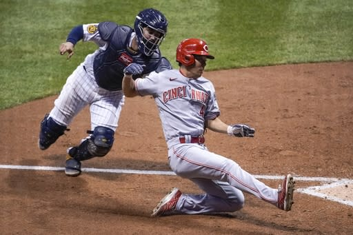 Milwaukee Brewers catcher Omar Narvaez tags out Cincinnati Reds' Shogo Akiyama at home during the seventh inning of a baseball game Saturday, Aug. 8, 2020, in Milwaukee. Akiyama tried to score from third on a ball hit by Joey Votto. (AP Photo/Morry Gash)