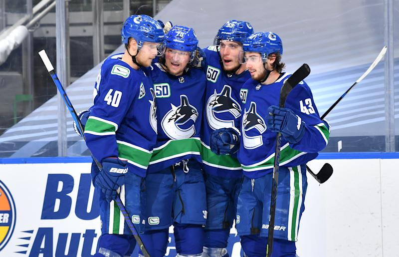 EDMONTON, ALBERTA - AUGUST 30: Tyler Toffoli #73 of the Vancouver Canucks celebrates with Elias Pettersson #40, Quinn Hughes #43 and Bo Horvat #53 after Toffoli scored in the second period of Game Four of the Western Conference Second Round of the 2020 NHL Stanley Cup Playoff between the Vegas Golden Knights and the Vancouver Canucks at Rogers Place on August 30, 2020 in Edmonton, Alberta. (Photo by Andy Devlin/NHLI via Getty Images)