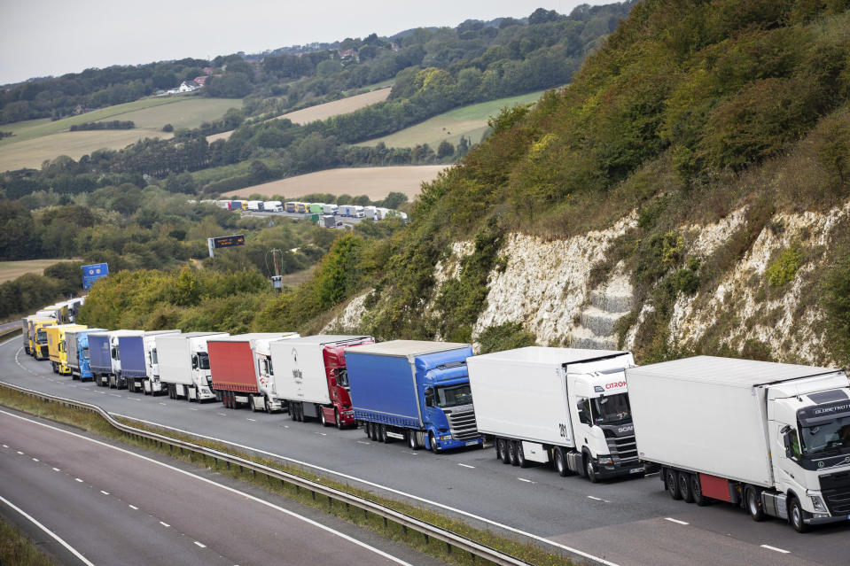Heavy goods vehicles queue on a main road near Dover, southern England, after a police operation in the port city resulted in traffic congestion on nearby roads, Wednesday Sept. 16, 2020.  Authorities deployed the planned Operation Stack along main roads to cope with heavy traffic approaching the channel port to transit to mainland Europe.  (Aaron Chown/PA via AP)