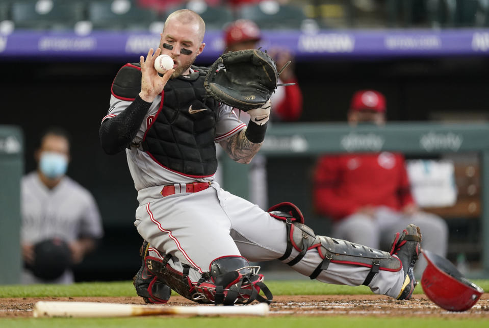 Cincinnati Reds catcher Tucker Barnhart holds up the ball after tagging out Colorado Rockies' Connor Joe during the first inning of a baseball game Thursday, May 13, 2021, in Denver. (AP Photo/David Zalubowski)