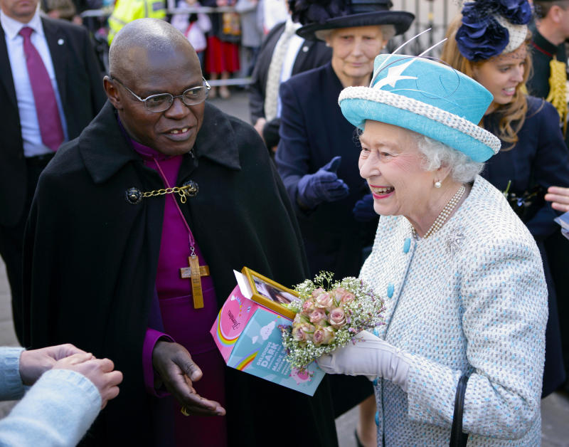 YORK, UNITED KINGDOM - APRIL 05: (EMBARGOED FOR PUBLICATION IN UK NEWSPAPERS UNTIL 48 HOURS AFTER CREATE DATE AND TIME) Queen Elizabeth II (accompanied by Dr John Sentamu, The Archbishop of York) is presented with an Easter Egg by a member of the public during a walkabout outside the Mansion House whilst on a visit to York, after attending the Maundy Thursday Church Service at York Minster on April 5, 2012 in York, England. (Photo by Indigo/Getty Images)