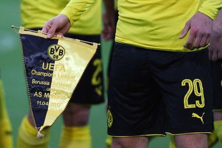 Borussia Dortmund's Marcel Schmelzer holds a pennant with yesterdays date on before the match