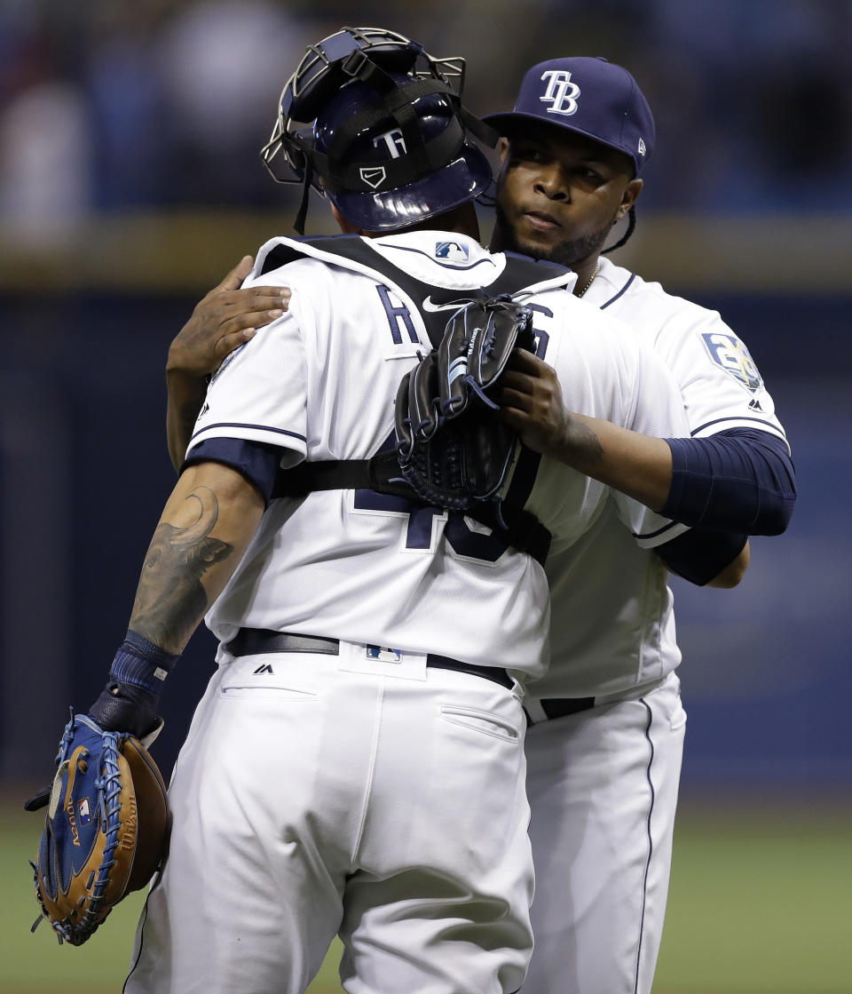 Tampa Bay Rays relief pitcher Alex Colome, right, hugs catcher Wilson Ramos after the Rays defeated the Boston Red Sox 6-4 during a baseball game Thursday, March 29, 2018, in St. Petersburg, Fla. (AP Photo/Chris O'Meara)