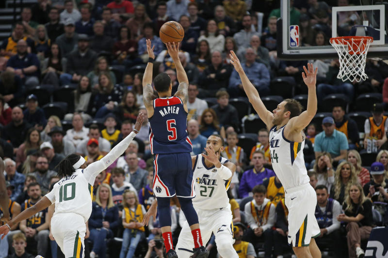 Washington Wizards guard Shabazz Napier (5) shoots as Utah Jazz's Mike Conley (10), Rudy Gobert (27) and Bojan Bogdanovic (44) defend in the first half during an NBA basketball game Friday, Feb. 28, 2020, in Salt Lake City. (AP Photo/Rick Bowmer)