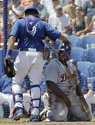 Toronto Blue Jays catcher J.P. Arencibia (9) taps Detroit Tigers first baseman Prince Fielder on the helmet after he tagged Fielder out at the plate on Jhonny Peralta's third-inning single during their spring training baseball game in Dunedin, Fla., Tuesday, April 3, 2012. (AP Photo/Kathy Willens)