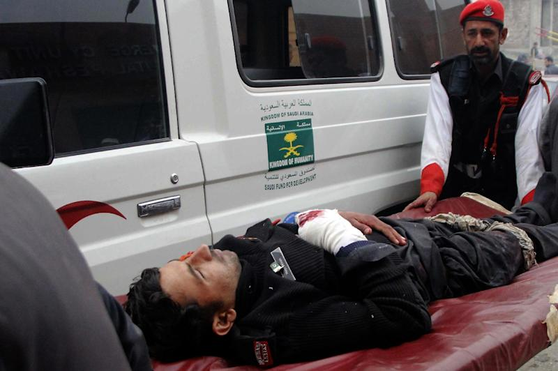 Staff shift an injured security officer to emergency ward at a hospital in Peshawar, Pakistan, Wednesday, Feb. 15, 2017. A Taliban suicide bombing targeted the administrative headquarters of a tribal region in northwestern Pakistan on Wednesday, killed scores of policemen and two passers-by, according to officials. (AP Photo/Mohammad Sajjad)